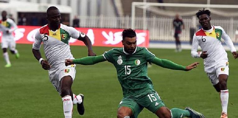 Photo: Algeria's Hilal Soudani (C) vies with Guinea's Fode Camara (L) during the friendly football match Algeria versus Equatorial Guinea.