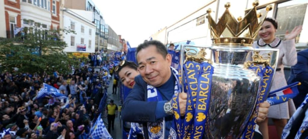 """Vichai holding the Premier League trophy during the victory parade in 2016 to celebrate Leicester City FC's remarkable achievement."""